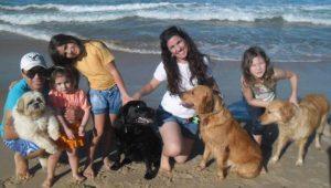 Havaiana (Schwarzer Labrador) und Lua (Golden Retriever, sitzend) in der Freizeit mit der Patenfamilie am Strand
